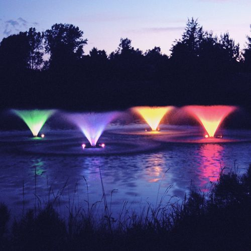 four small colored fountains in pond